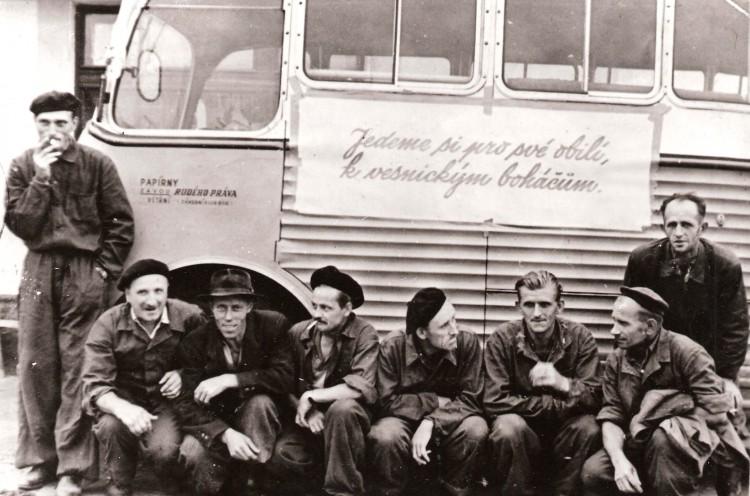 """02. Dělníci z Větřní u autobusu s nápisem """"Jedem si pro své obilí k vesnickým boháčům""""."""