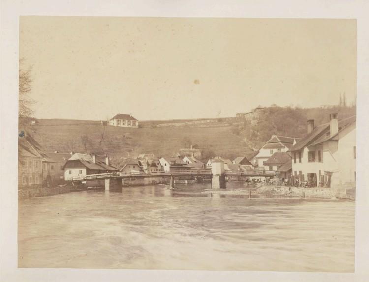 6. Gotthard Zimmer, nedatováno, před 1883.  Unikátní, jedna z nejstarších fotografií lokality. V roce 1883 byla vystavěna škola v Linecké č. p. 43. Na jejím místě stávaly dva renesanční domy zachycené na fotografii, které musely stavbě ustoupit. Kájovský most (dnes Edvarda Beneše) prošel několika obměnami - od dřevěného se zděnou kapličkou, přes nýtovaný kovový z roku 1889, po dnešní, železobetonový z roku 1937. (soukromá sbírka)